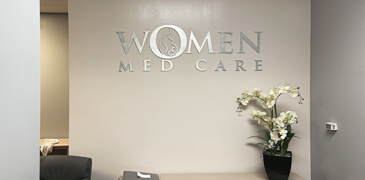 Women Med Care clinic reception sign made of aluminum