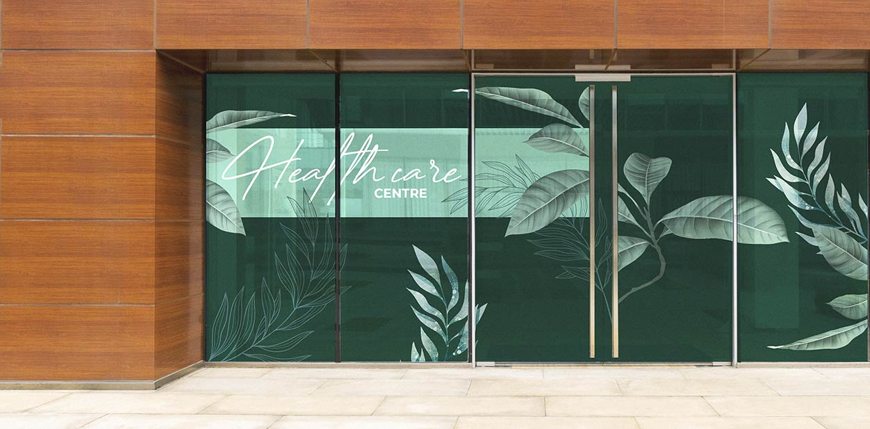 Medical office window design idea with green nature-themed graphics