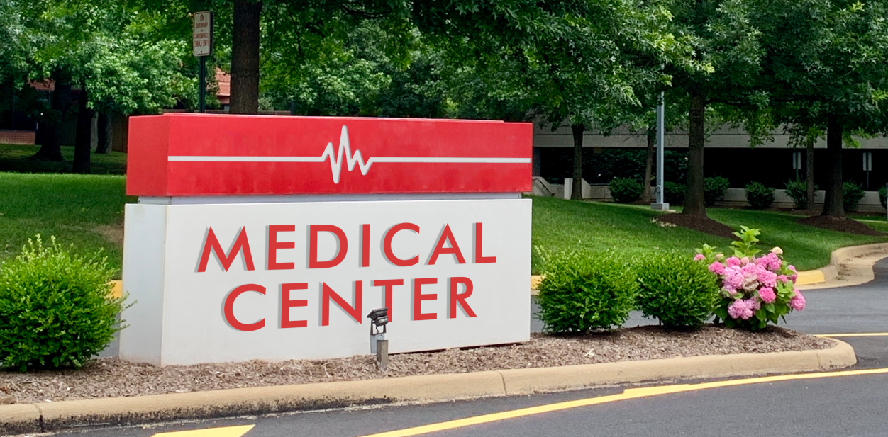 Red and white colored monumental medical board displayed outdoors