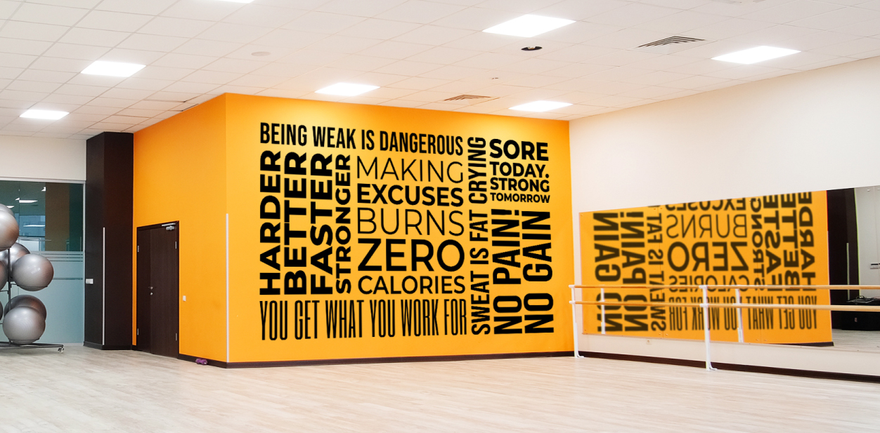 Different motivational gym sign phrases displayed on a yellow wall