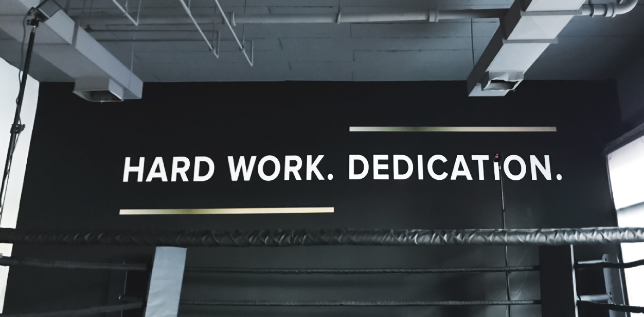 Motivational gym sign displaying the phrases Hard Work and Dedication