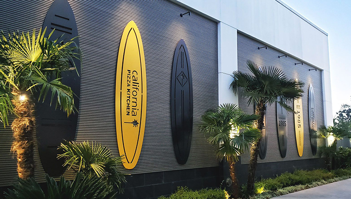 California Pizza Kitchen metal outdoor signs in yellow and black surfboard shapes
