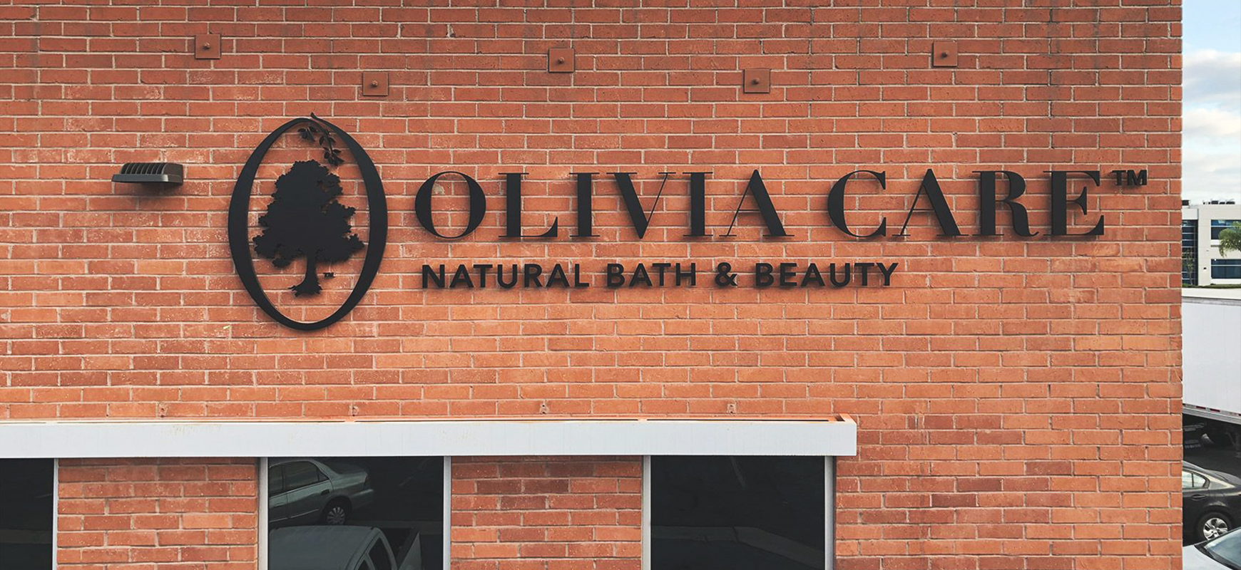 Olivia Care high rise exterior sign in black made of acrylic