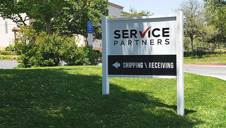 Service Partners free-standing outdoor sign made of Dibond and wood displayed at the yard