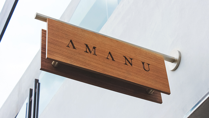 Amanu wooden outdoor sign displaying the brand name in an engraved style