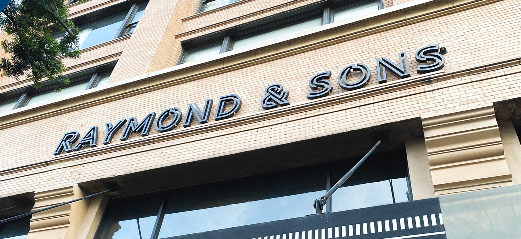 Raymond and Sons outdoor architectural signage made of aluminum for storefront branding