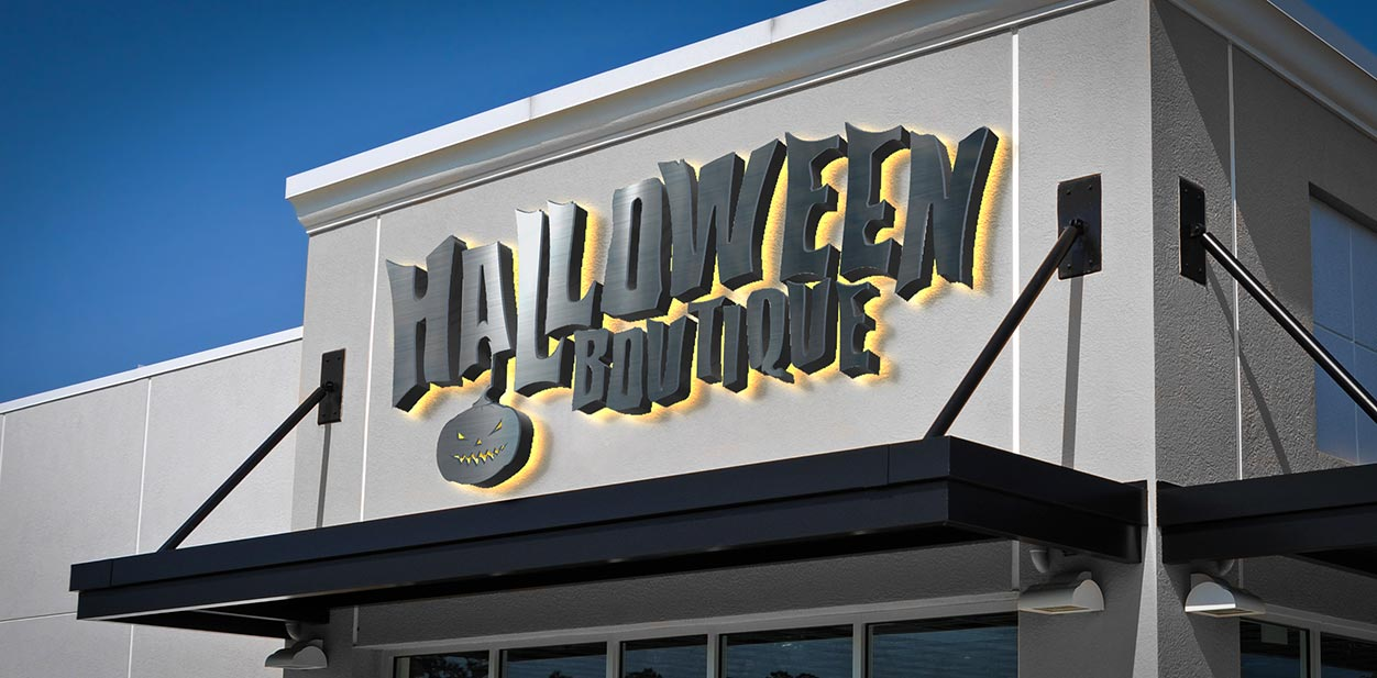 Lighted Halloween storefront sign in black displaying the boutique name