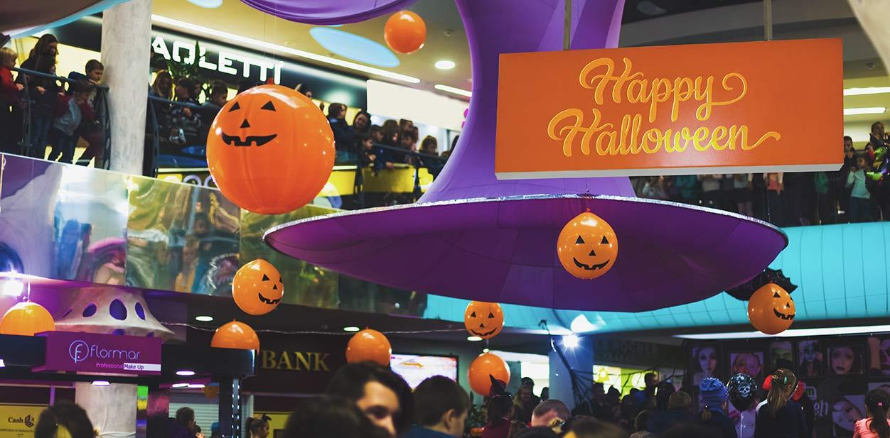 Hanging Halloween store signage and decorative pumpkins in orange