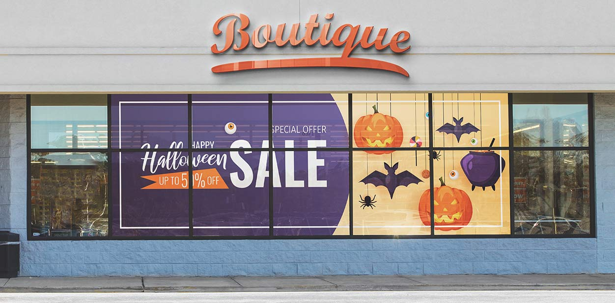 Large Halloween sign with holiday themed graphics displayed on the window