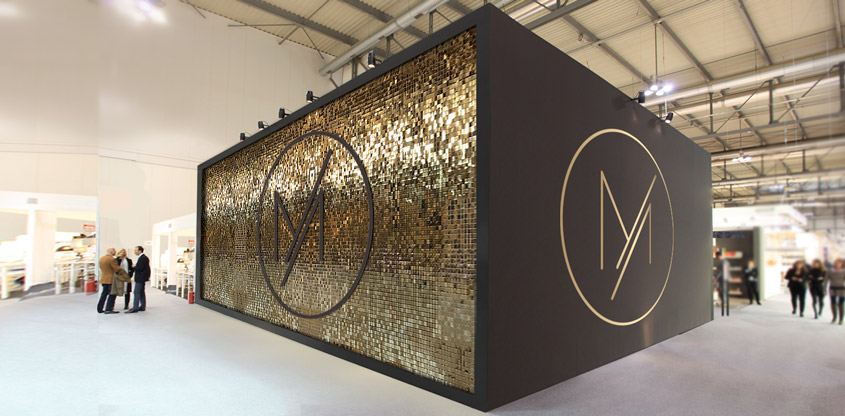 Golden shimmer wall with a brand logo for trade show booth design